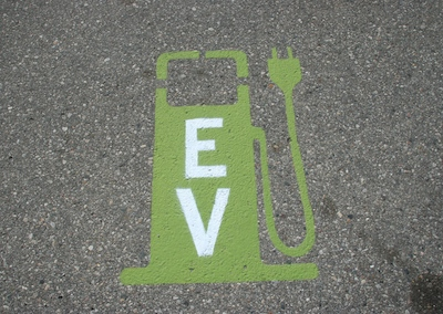 A painted sign on a street designating a spot to recharge a vehicle